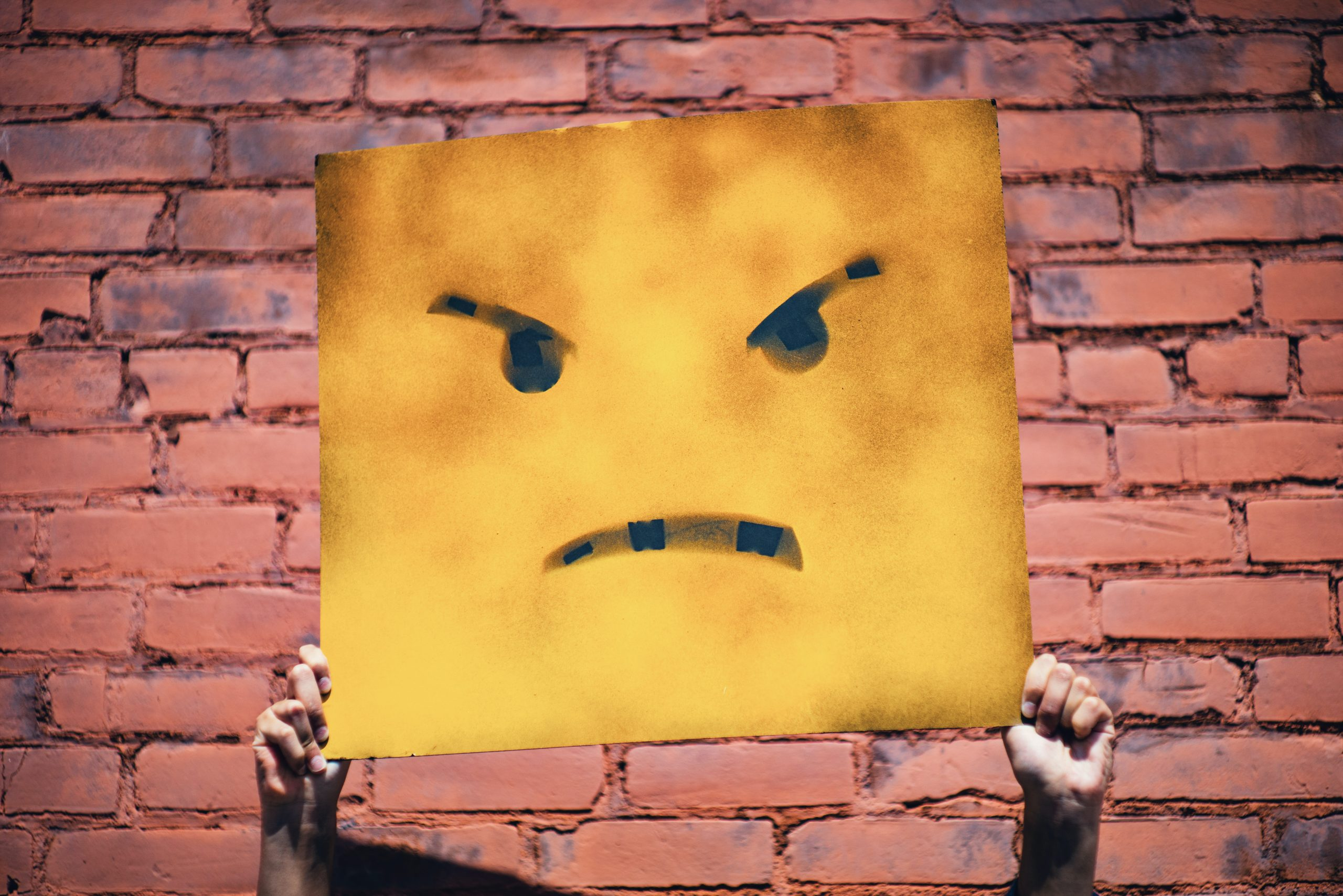 Hands holding sign with angry face on it