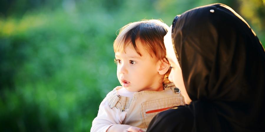 Мусульманка в хиджабе держит на руках ребёнка