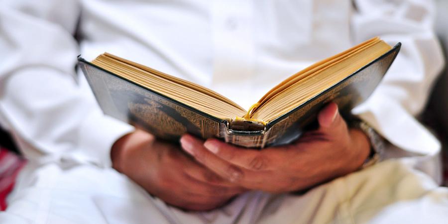 Мусульманин в белой одежде читает Коран