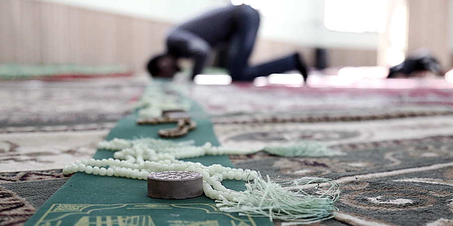 Мужчина читает намаз в шиитской мечети