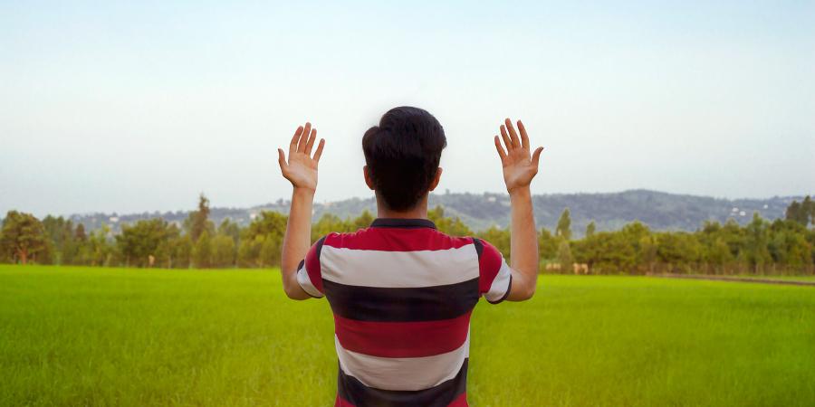 Молящийся в поле иранский парень
