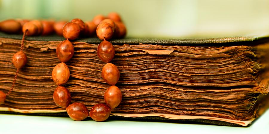 Коричневые чётки на старинном Коране