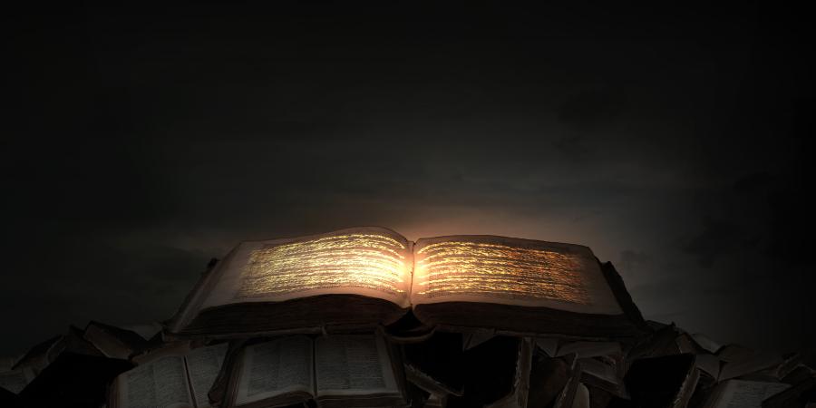 Открытая книга со святящимися буквами