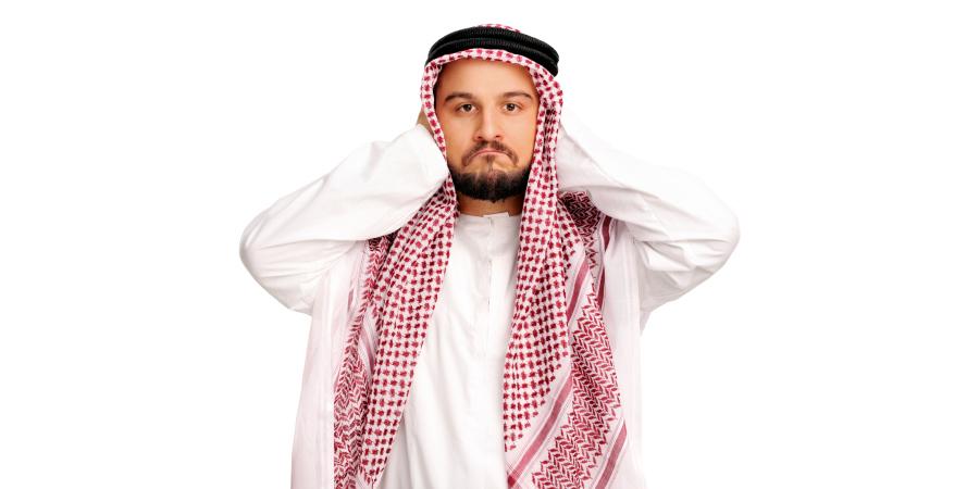 Мужчина в национальной арабской одежде, заткнувший уши руками