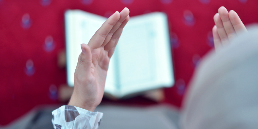Мусульманка, молящаяся над открытым Кораном