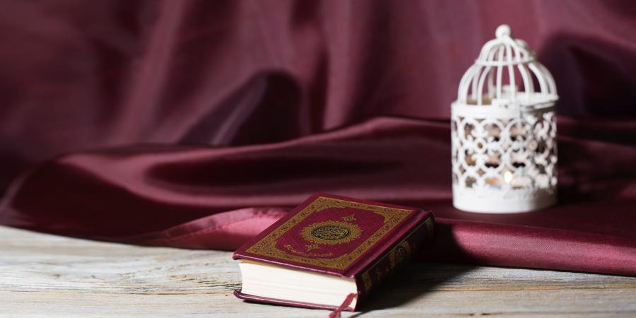 Коран в красной обложке рядом со светильником