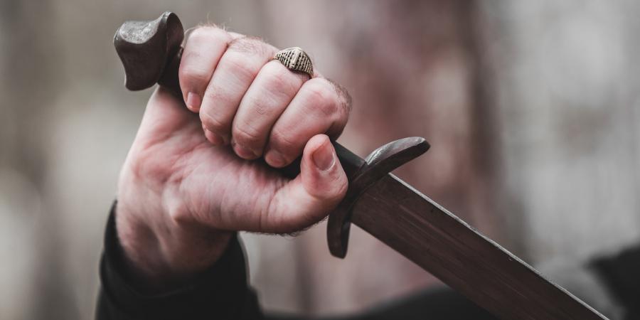 Рука мужчины, держащая меч