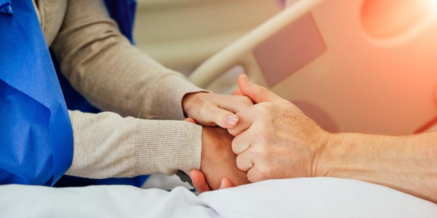 Женщина, держащая за руки мужчину в больничной койке