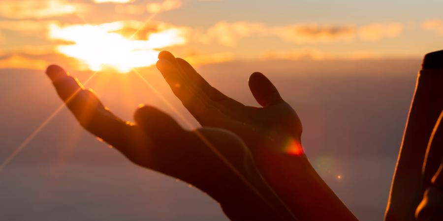 Мужчина, молящийся на фоне солнца