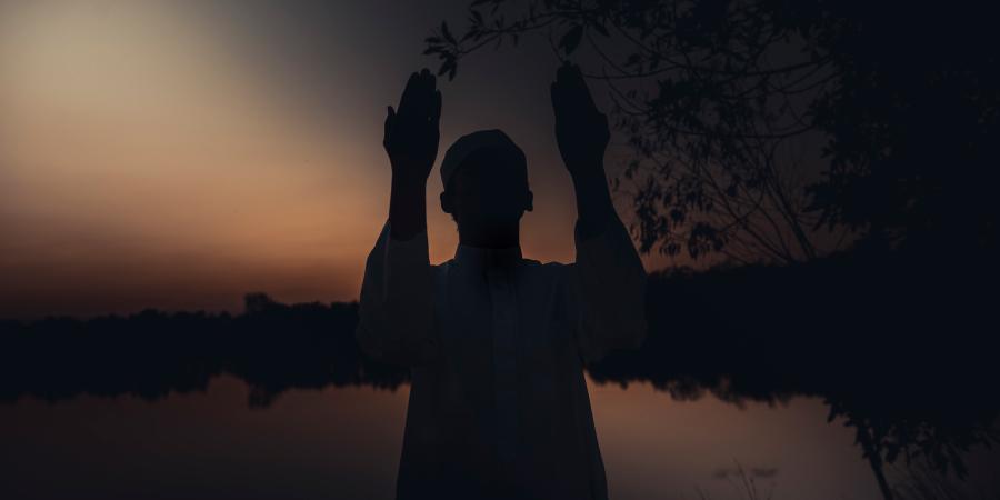 Мусульманин, молящийся в сумерках возле озера