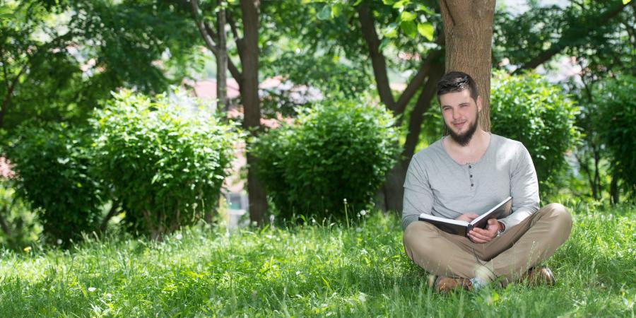 Мусульманин, сидящий под деревом с открытым Кораном