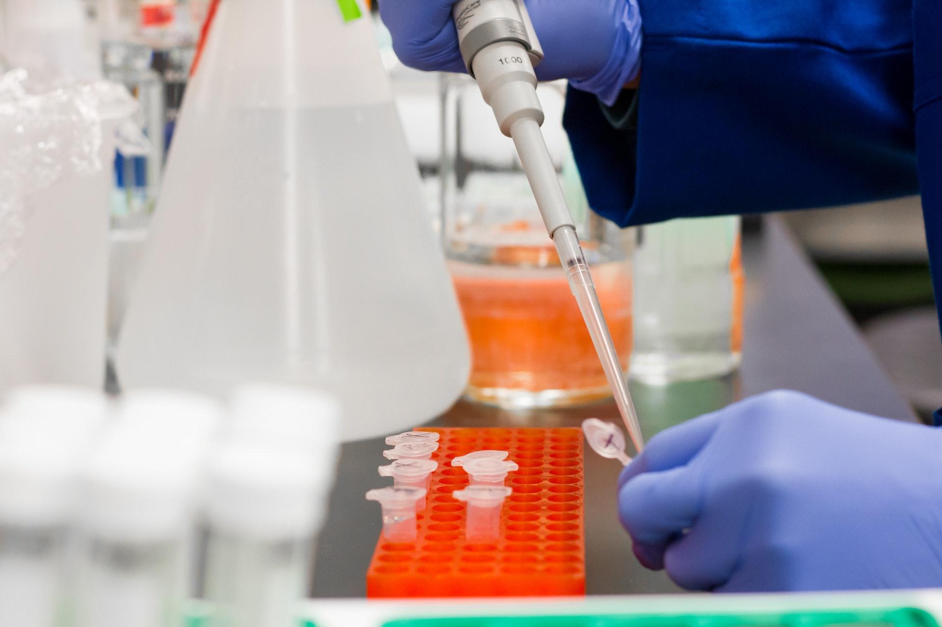 scientist putting a drop in a test tube