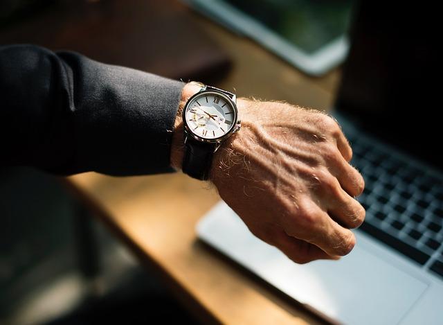 腕時計で時間を確認する男性