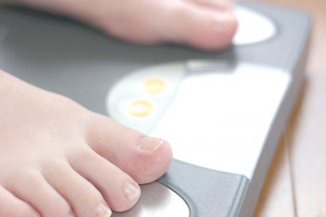 体重計に乗って体重を測る人
