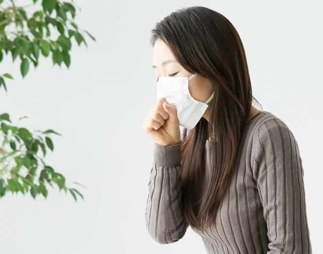 マスクを付けて咳をする女性