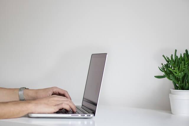 ノートパソコンを操作する男性の手