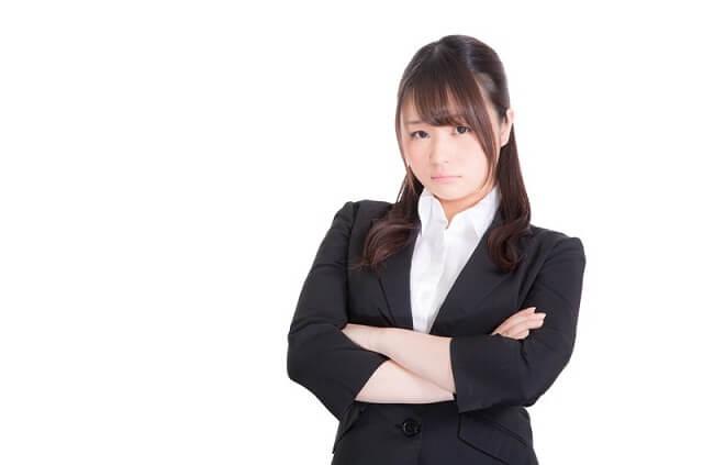 腕を組み考えるスーツ姿の女性