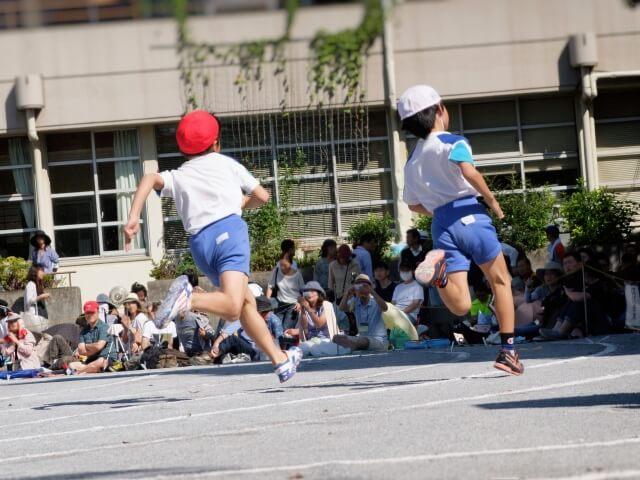 運動会でかけっこをする小学生の後ろ姿