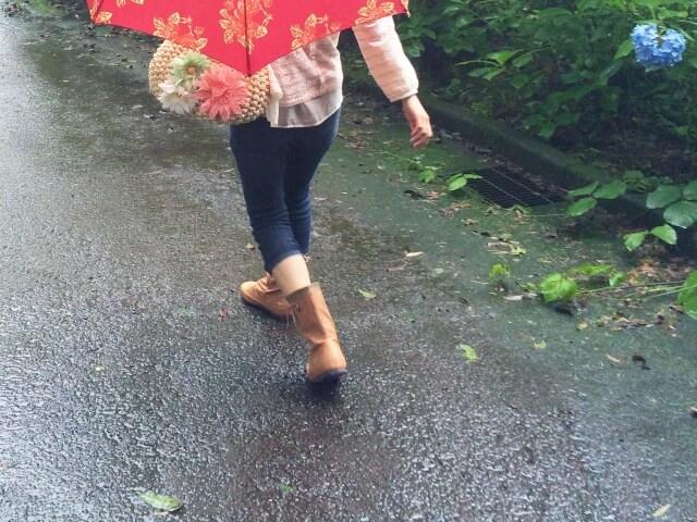 雨の日に傘をさして外を歩く女性