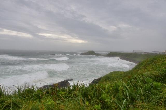 台風で曇った空と荒れた海