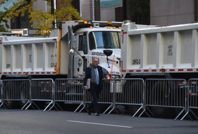 A man walks near a protective barrier of Sanitation Department trucks parked in front of Trump Tower on 5th Avenue to provide security to US President-elect Donald Trump on November 10, 2016 in New York. / AFP / TIMOTHY A. CLARY (Photo credit should read TIMOTHY A. CLARY/AFP/Getty Images)