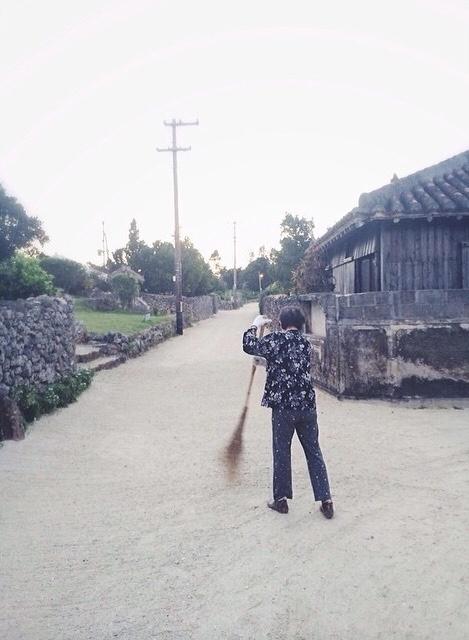 早朝の竹富島で朝掃除をしているおばあ