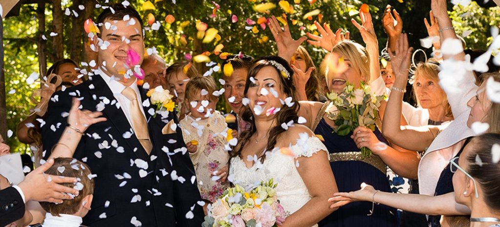 Guests greeting the new Bride and Groom with confetti