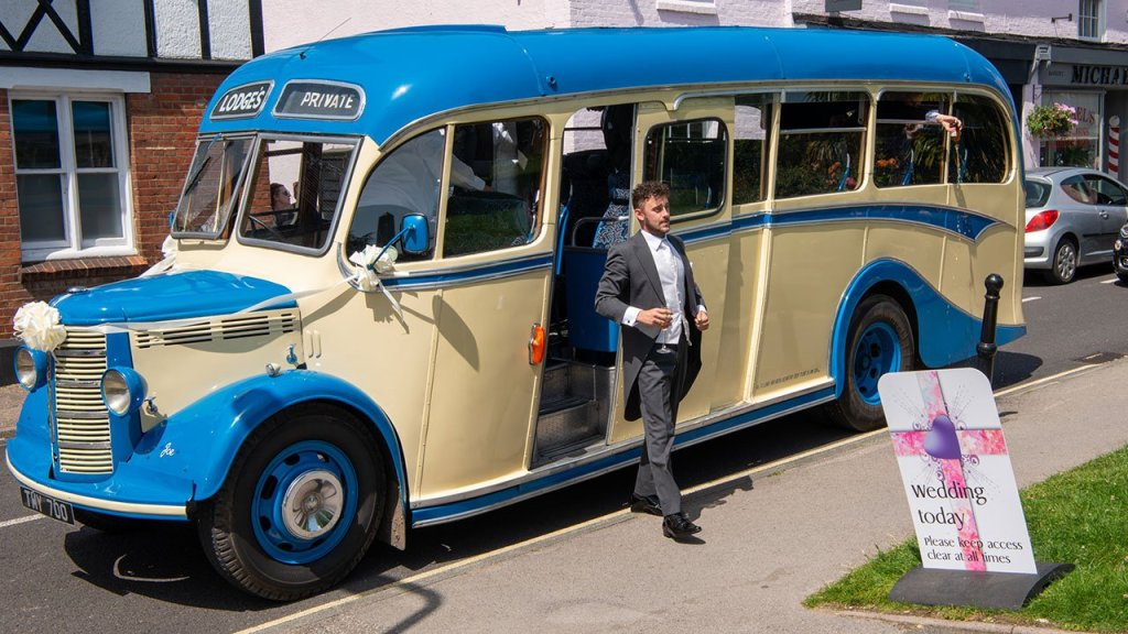 The Groom Arrives in style stepping off a 1949 vintage cream and blue bus wearing a grey tailed morning suit.