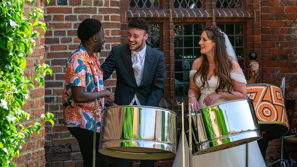 The Bride and Groom playing the steel drums with on of the band members