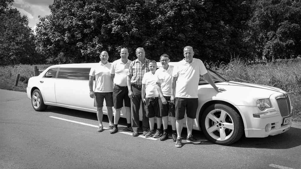 The Groom with the Father of the Bride and the other Grooms men standing by the limo