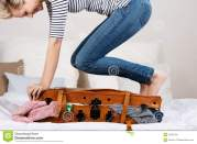 cheerful-woman-packing-suitcase-bed-midsection-young-smiling-31350755