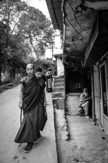"""""""Love and compassion are necessities, not luxuries. Without them, humanity cannot survive.""""― Dalai Lama A Buddhist monk walks through a narrow alley while a Hindu Sadhu sits by a local store along McLeod Ganj. There are over a billion people in India but the tolerance for other religions is fairly strong. Dalai Lama Temple, McLeod Ganj, Dharamsala India November 2015"""