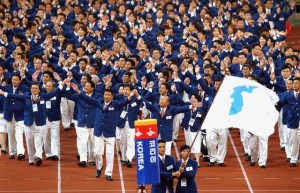 FILE - In this Sept. 29, 2002 file photo, athletes from North and South Korea march together, led by a unification flag during opening ceremonies for the 14th Asian Games in Busan, South Korea. Seven months ahead of the Pyeongchang Olympics, many in South Korea, including new liberal President Moon Jae-in, hope to use the Games as a venue to promote peace with rival North Korea. To do so, the North's participation is essential, but an ongoing nuclear tension and a lack of winter sports athletes in North Korea could ruin the attempts at reconciliation. (Yonhap via AP, File)
