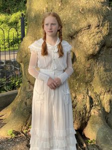 Anna Mary wearing her great-great grandmother's dress and standing in front of the Sycamore at the Snyder-Hershey