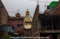 Boudhanath Stupa as seen from the west through the urban building at the foreground. The construction of these urban buildings around the nearby territory of Boudhanath is a common here. Boudhanath stupa is a UNESCO listed world Heritage site.