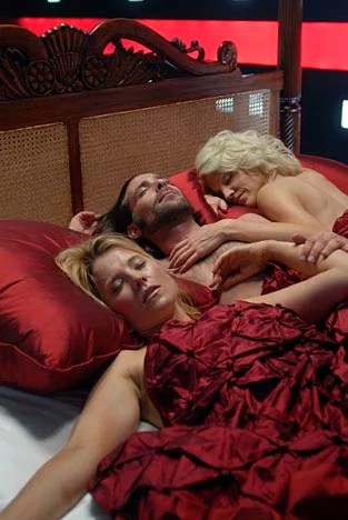Two lady robots lay entwined with a bloke in red sheets.