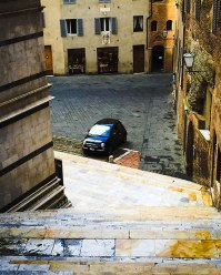 A bit of a classic Italian scene, though a bit of a modern touch: a Fiat parked in a Piazza.