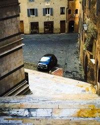 A bit of a classic Italian scene, though a bit of a modern touch: a Fiat parked in a Piazza.