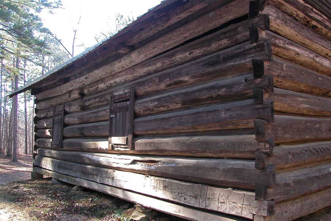 Note how the logs are notched to securely interlock and force rainwater to flow toward the outside. The bottom two logs on the window side are replacements.