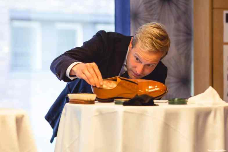 Niclas Andersson, part of the jury, examines a contestants shoe.