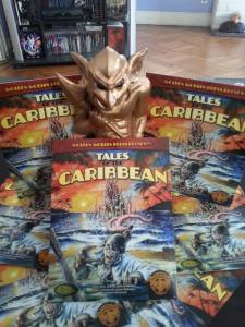 "Image is 5 books laid out in presentation around a statuette of a golden goblin. The books itself features the text ""Tales of the Caribbean"" it features a man approaching the bottom edge of the cover with the ocean extending up behind him. In the ocean is some sort of tentacled thing with tentacles reaching towards him."