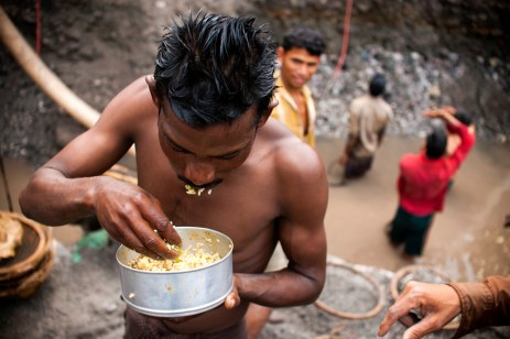 An worker having his food. Most of them had rice with simple gravy or vegetable and no protein what so ever.