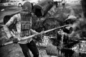 A worker pouring molten asphalt.