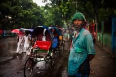 A rain soaked rickshaw puller.
