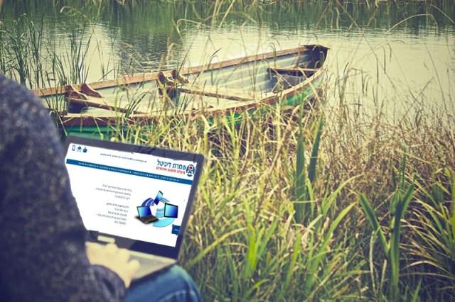 שמרת דיגיטל - איש עם מחשב ליד  אגם מבצע תמיכה מרחוק