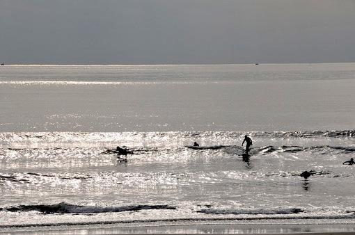 冬の曇り空の江ノ島片瀬西浜とサーファー