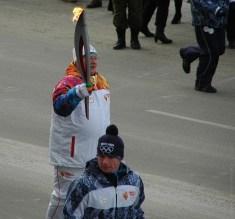 Факелоносца окружают суровые бегуны в синевато-серых куртках