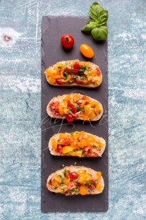 Baguettescheiben mit Bruschetta aus bunten Tomaten, Basilikum,