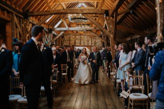 The bride enters the ceremony room at Bassmead Manor Barn