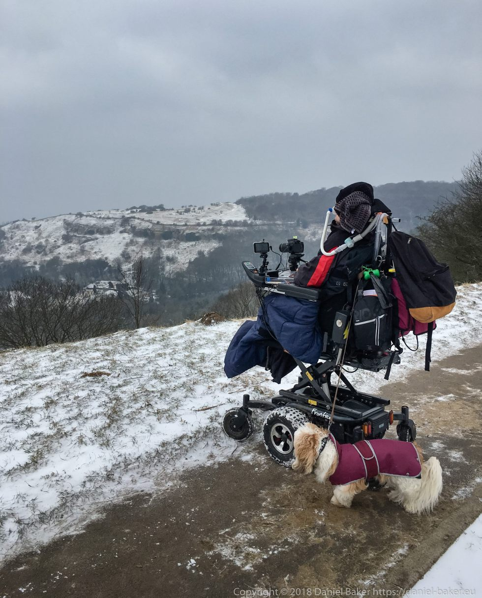 Daniel Baker looking down over Cheltenham from Birdlip hill in the snow, attached to his wheelchair is his faithful dog Mya